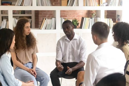a group therapy session discussing drug rehab centers