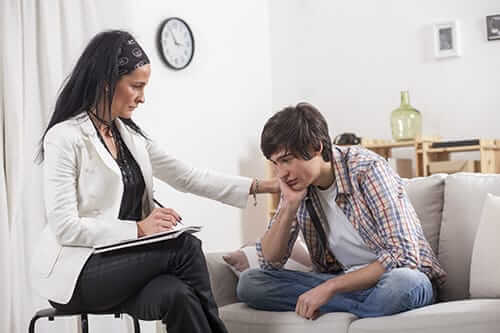 Female counselor talking to upset young man at our opiate addiction treatment center