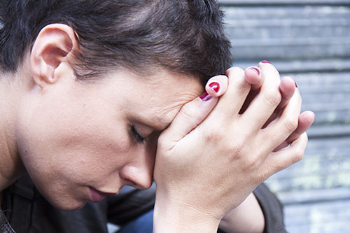 Depressed woman clasping hands looking for an oxycontin addiction treatment center
