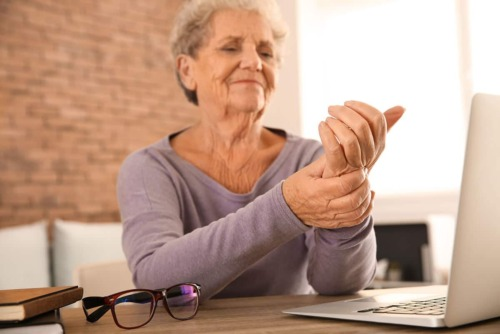 older woman sits at computer and rubs her hand to try and alleviate the symptoms of rheumatoid arthritis